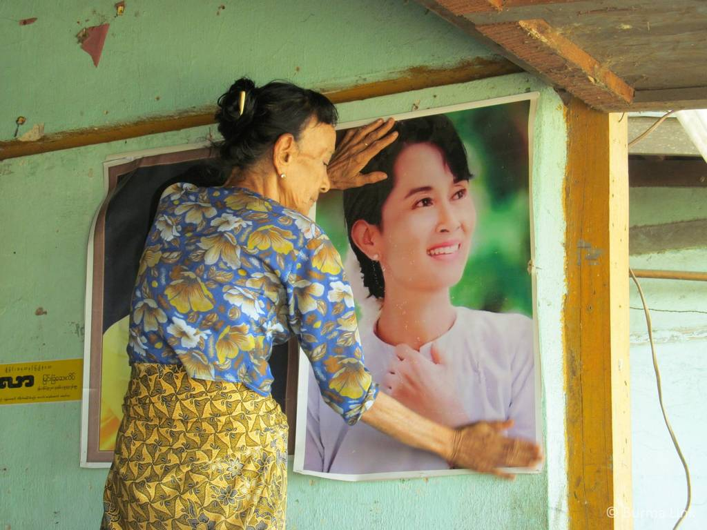 Woman hanging a poster of Aung San Suu Kyi in Rangoon